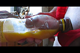 MILKING IN BOTTLE OF ORANGE JUICE